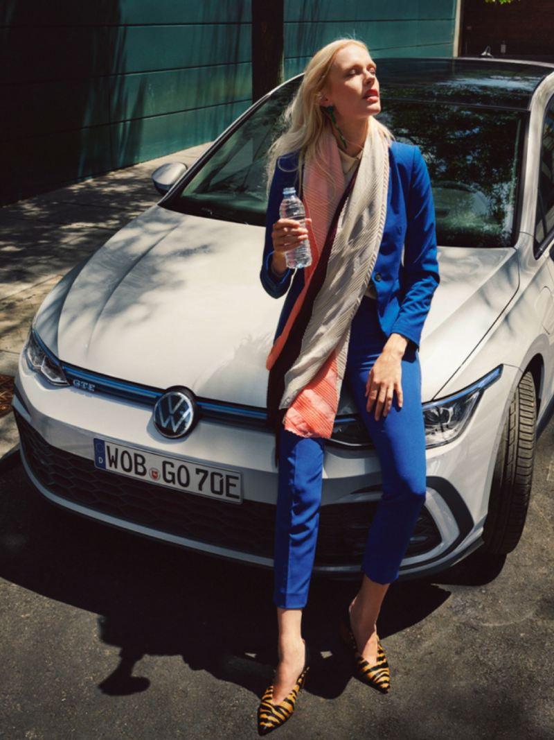 Mujer vestida de azul con una botella de agua sentada en el capó de un Volkswagen Golf GTE blanco