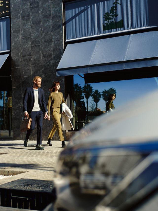 Pareja caminando por la acera detrás de un fragmento del faro de un Volkswagen Passat GTE fuera de foco