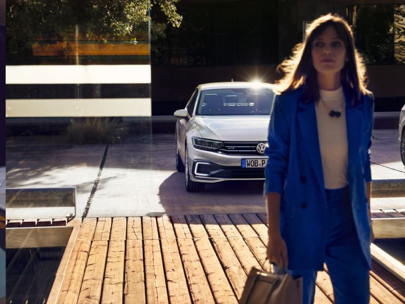 Mujer vestida de azul caminando delante de un Volkswagen Passat GTE blanco aparcado