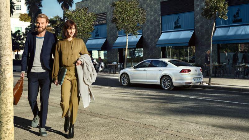 Pareja caminando delante de un Volkswagen Passat GTE blanco aparcado en la ciudad