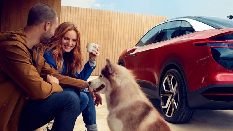 Pareja sentada con un perro delante de un Volkswagen ID. Crozz aparcado