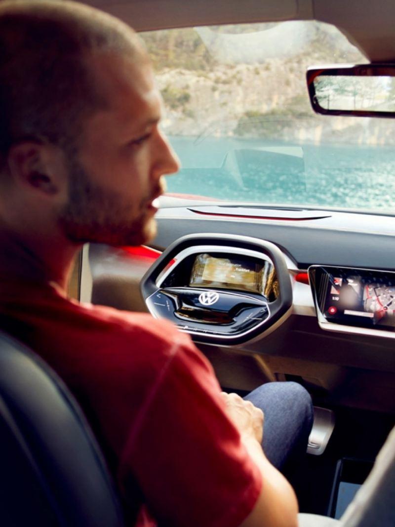 Detalle del volante y salpicadero de un Volkswagen ID. Crozz con un chico en primer plano fuera de foco