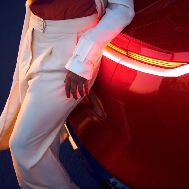 Detalle del piloto trasero de un Volkswagen ID. Crozz y de una mujer vestida de blanco apoyada