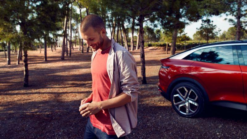 Hombre delante de un ID. Crozz aparcado en un bosque