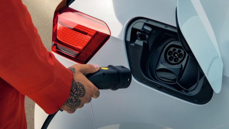 Detalle de una mano conectando un cargador a un Volkswagen eléctrico