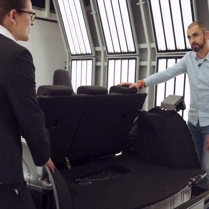 Dos hombres mirando la parte de atrás de la plataforma MEB de Volkswagen con los asientos instalados
