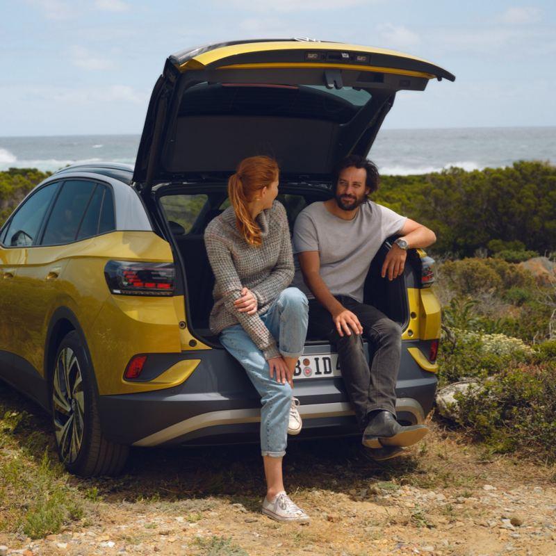 Una pareja sentada en el maletero abierto de un Volkswagen ID.4 amarillo en el campo