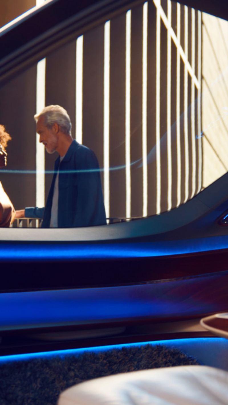 Pareja de pie hablando vista desde el interior de un Volkswagen azul