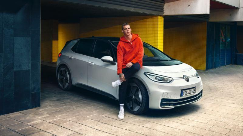 Chico apoyado en un Volkswagen ID.3 blanco aparcado en casa