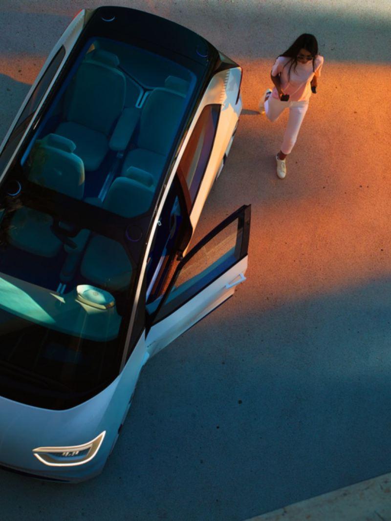 Vista cenital de una mujer caminado hacia un Volkswagen ID.Buzz con la puerta del conductor abierta