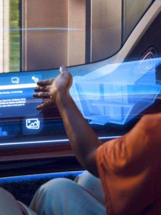 Mujer usando una interfaz gráfica 3D proyectada sobre el salpicadero de un Volkswagen