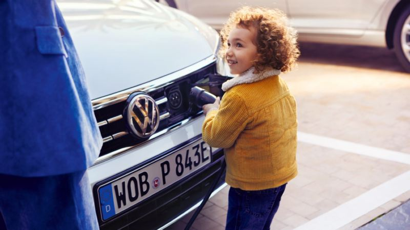 Niña con chaqueta amarilla conectando un cargador eléctrico a un Volkswagen híbrido