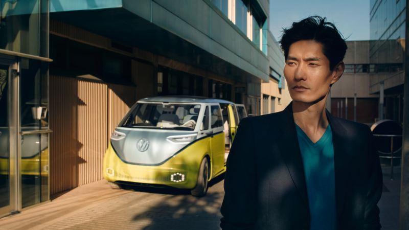 Hombre joven mirando al frente delante de un Volkswagen ID.Buzz aparcado en la ciudad