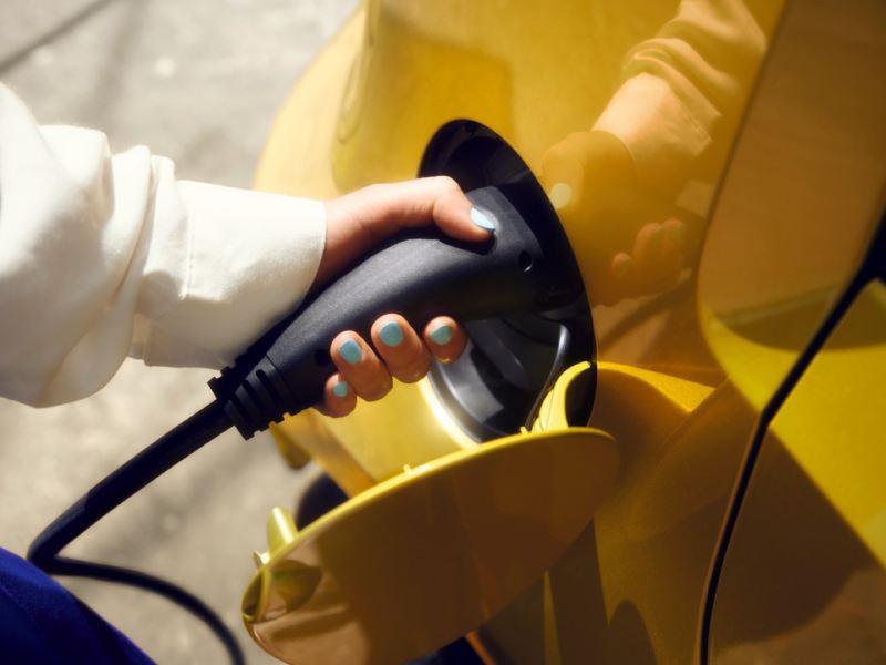 Detalle de la mano de una mujer conectando un cargador a un Volkswagen eléctrico amarillo