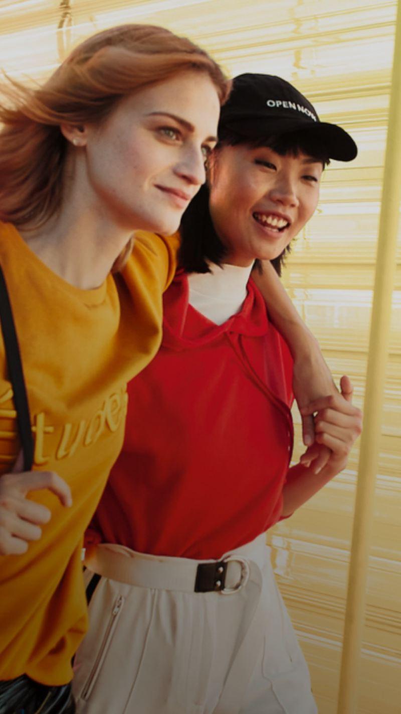 Dos chicas jóvenes caminando abrazadas y sonriendo sobre un fondo amarillo traslúcido