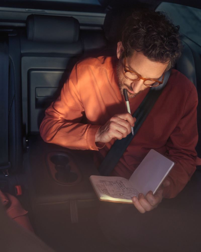 Hombre pensativo escribiendo en una libreta con el bolígrafo en la barbilla