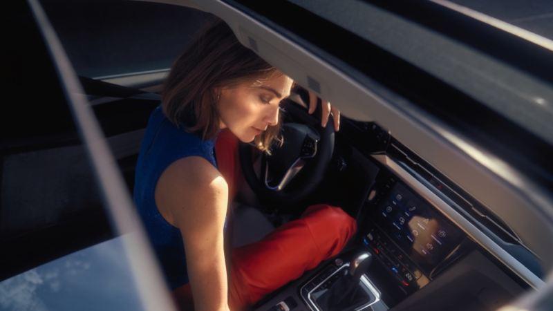 Chica entrando en un Nuevo Volkswagen Arteon vista desde la ventanilla del acompañante