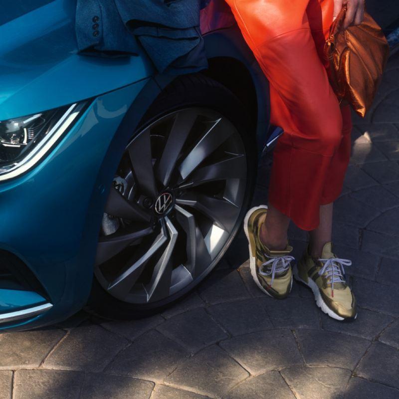 Chica apoyada junto a las ruedas de un Nuevo Volkswagen Arteon azul