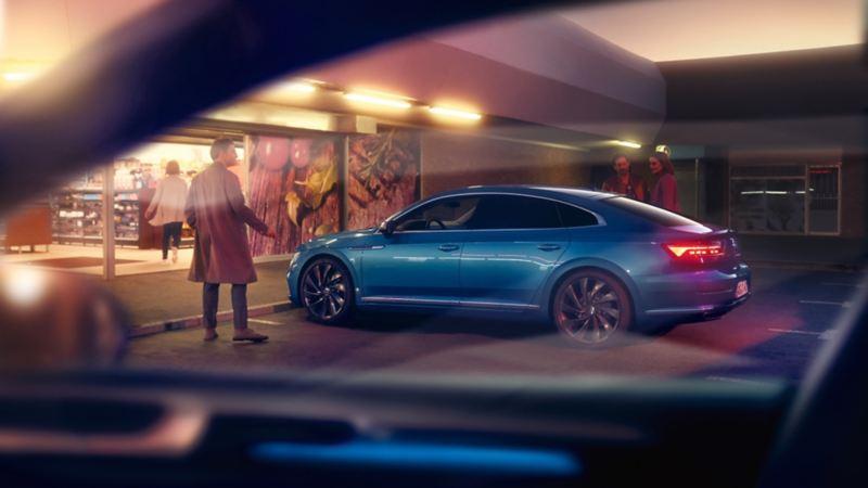 Hombre junto a un Nuevo Volkswagen Arteon azul aparcado en la calle por la noche