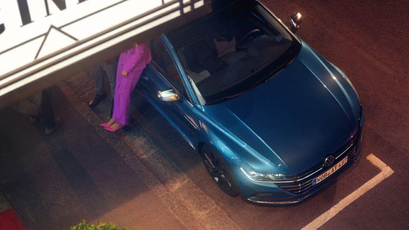 Vista superior de una pareja apoyada en un Nuevo Volkswagen arteon azul con los faros encendidos