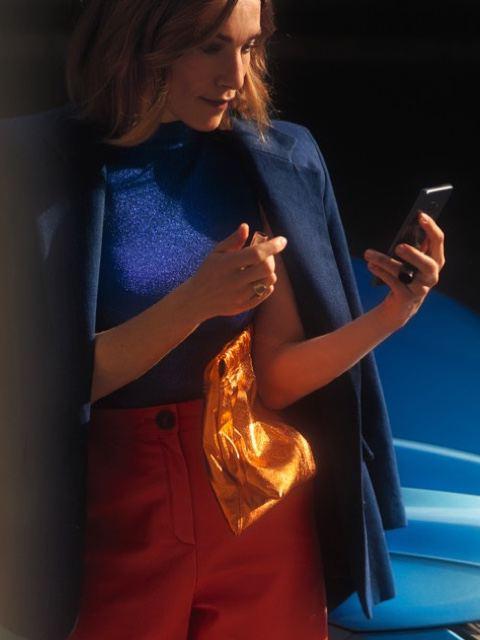 Chica mirando su teléfono móvil junto a un Nuevo Volkswagen Arteon azul