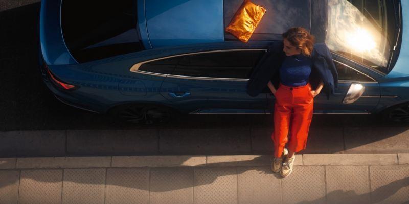Vista superior de una chica apoyada en un Nuevo Volkswagen azul aparcado en la calle