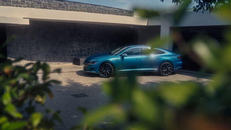 Nuevo Volkswagen Arteon azul aparcado en el porche de una casa visto a través de unas hojas