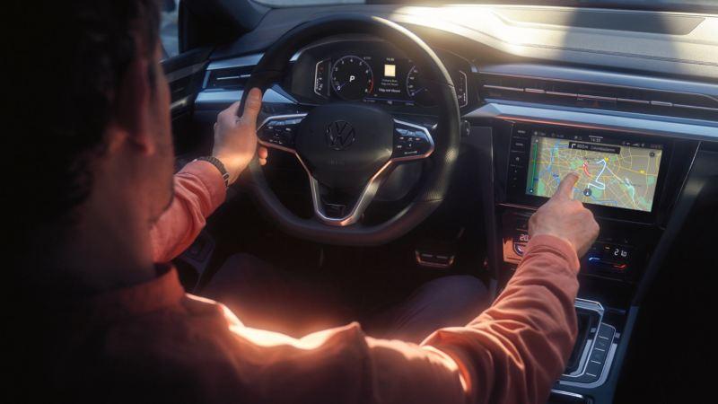 Hombre interactuando con la pantalla tactil del sistema de radionavegación Discover Pro de un Nuevo Volkswagen Arteon