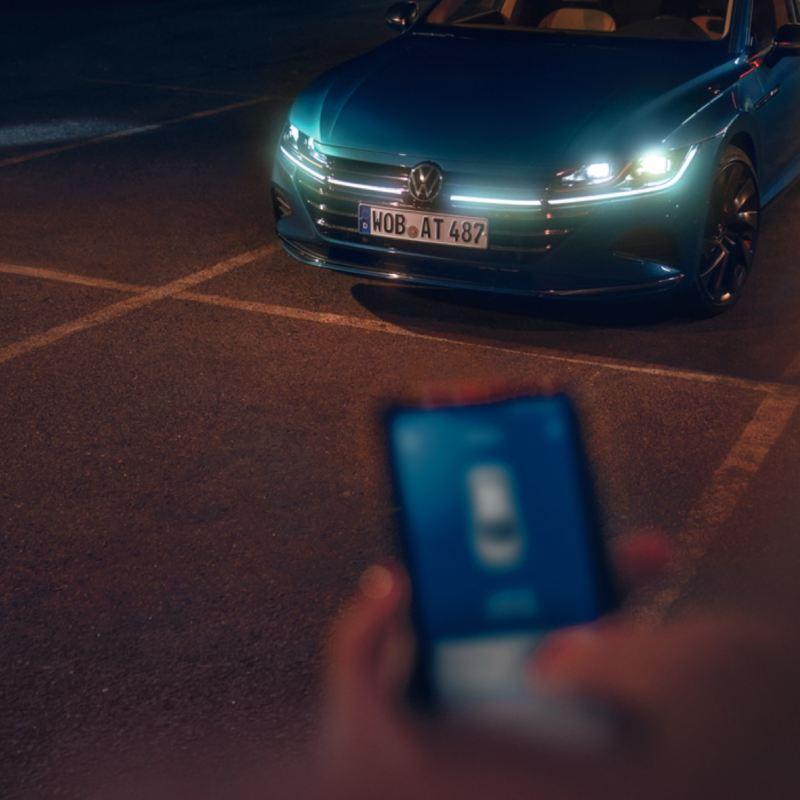 Vista subjetiva de la aplicación We Connect junto a un Nuevo Volkswagen Arteon azul