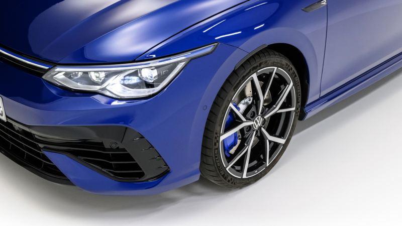 Detalle de un faro y la llanta de un Volkswagen Golf 8 R azul