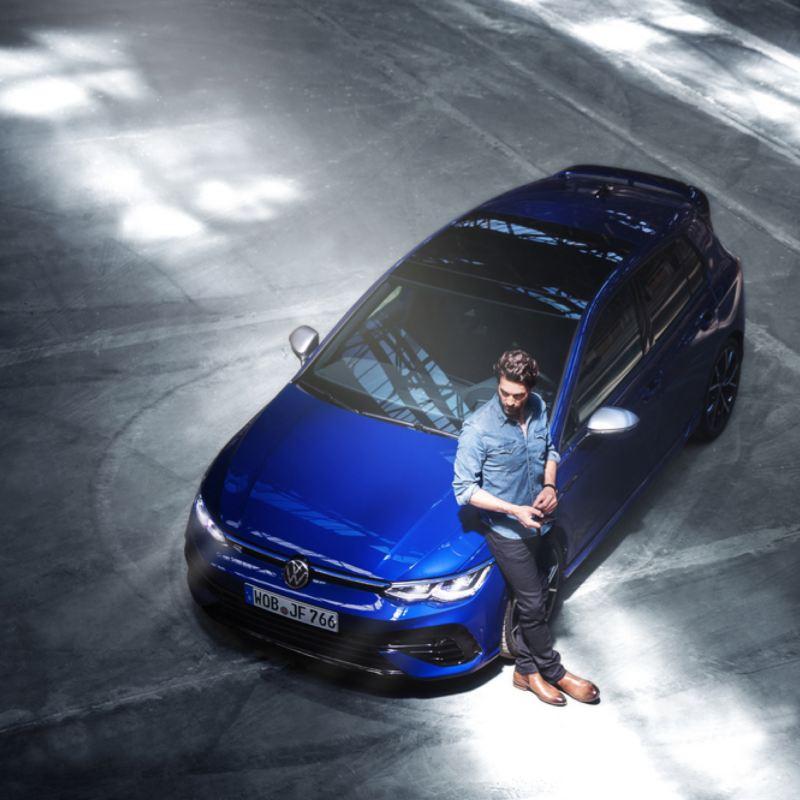 Hombre apoyado en un Volkswagen Golf 8 R azul visto desde arriba en un parking