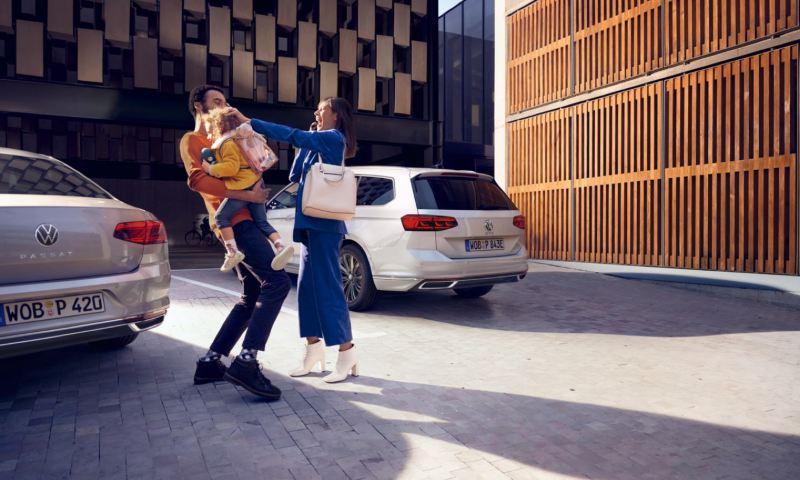 Madre y padre con su hija en brazos delante de dos Volkswagen Passat aparcados vistos desde atrás