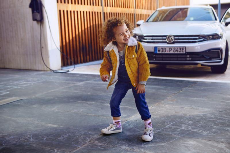 Niña sonriendo delante de un Volkswagen Passat GTE aparcado y conectado al cargador eléctrico