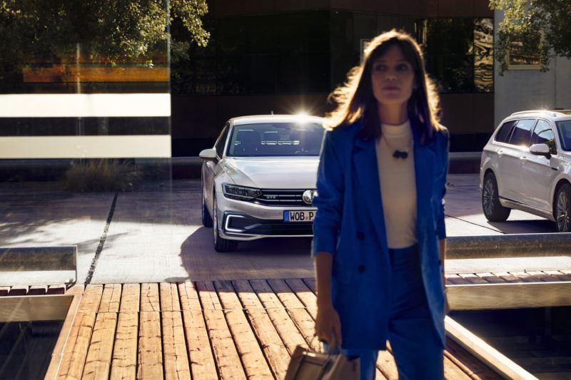 Chica desenfocada en primer plano delante de un Volkswagen Passat Variant GTE aparcado visto de frente