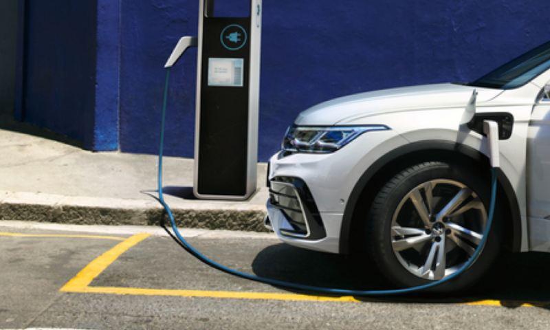 Detalle de un Volkswagen Tiguan eHybrid conectado a un cargador eléctrico en un parking