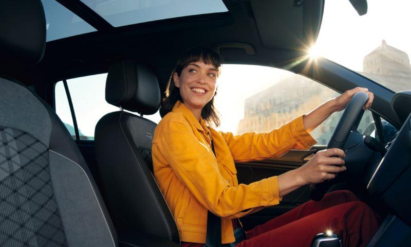 Chica con chaqueta amarilla sonriendo al volante de un Volkswagen Tiguan eHybrid