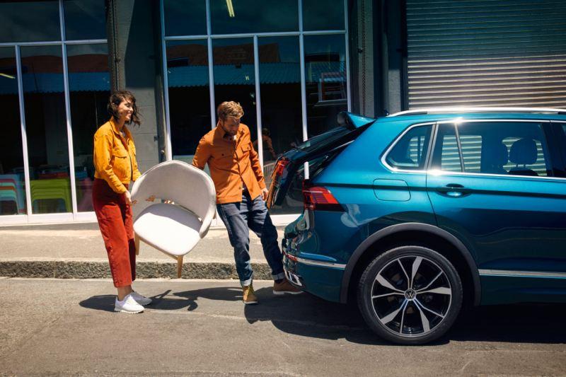 Una pareja con unas silla abriendo el portón trasero de un Volkswagen Tiguan eHybrid azul