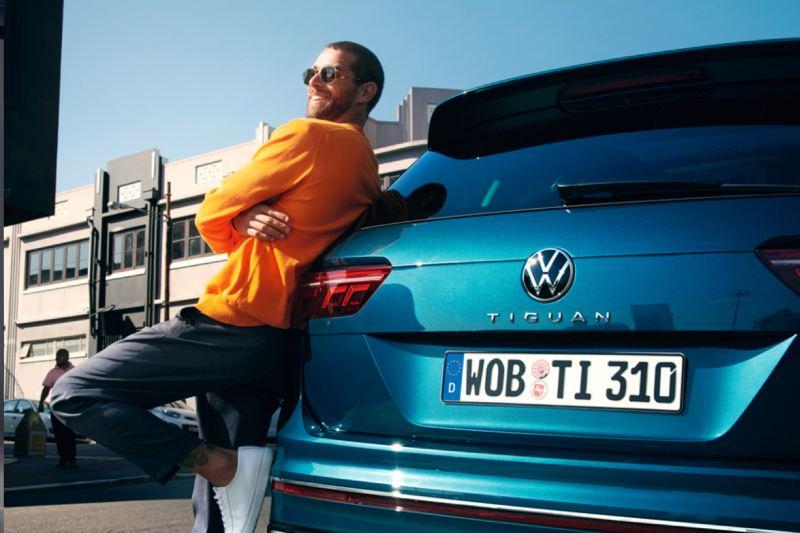 Chico sonriendo apoyado en la parte trasera de un Volkswagen Tiguan eHybrid azul