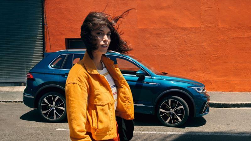Chica de amarillo de pie frente a un Volkswagen Tiguan eHybrid aparcado frente a un muro naranja
