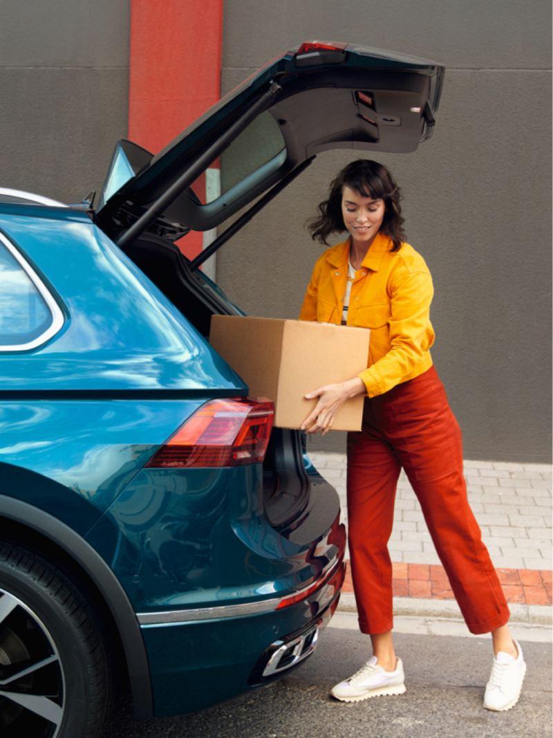 Chica cargando una caja en el maletero de un Volkswagen Tiguan eHybrid