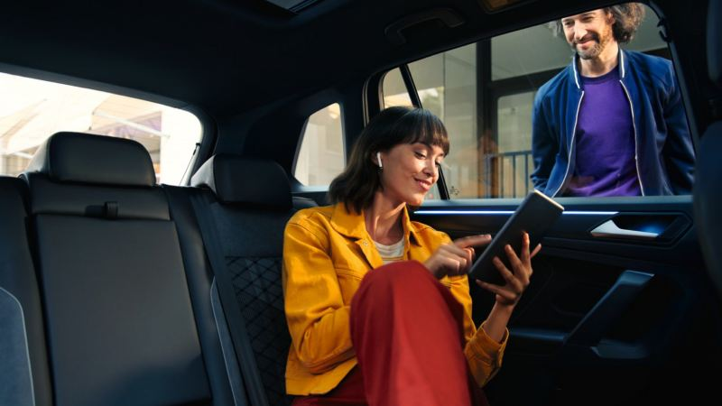 Chica con una tablet en el asiento trasero de un Volkswagen Tiguan mientras se ve a un chico a través de la ventana