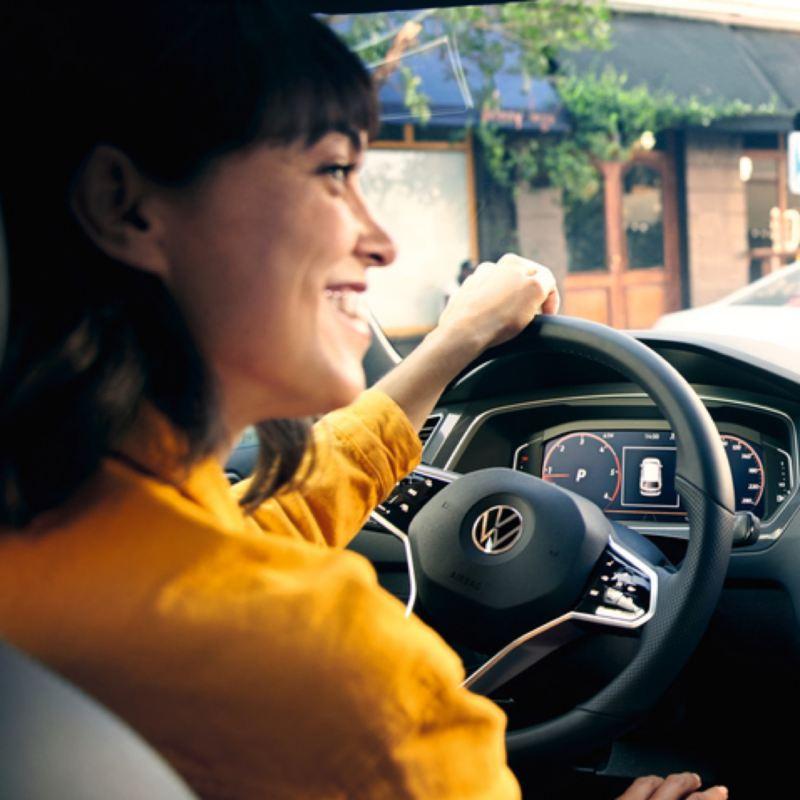 Primer plano de una chica vestida de amarillo conduciendo un Volkswagen Tiguan y el volante multifunción
