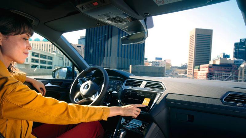 Chica dentro de un Volkswagen Tiguan usando la pantalla interactiva del salpicadero
