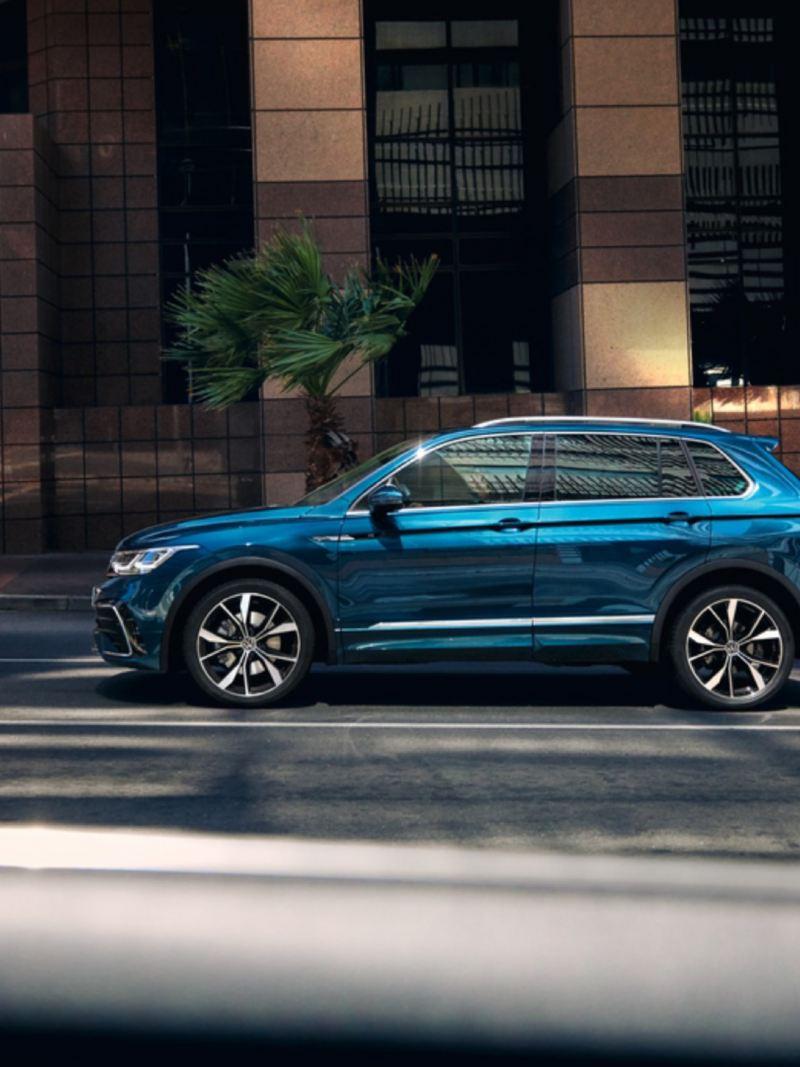 Volkswagen Tiguan azul metalizado visto de costado circulando por la ciudad