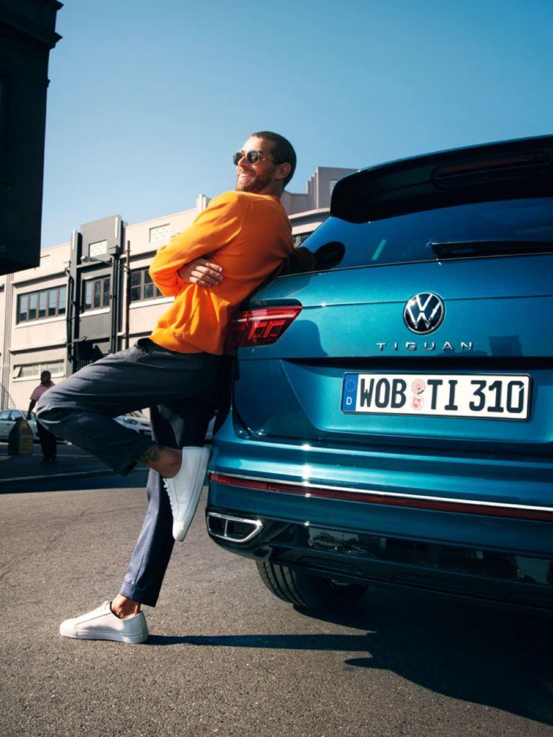 Hombre joven sonriendo apoyado en la parte trasera de un Volkswagen Tiguan azul metalizado aparcado