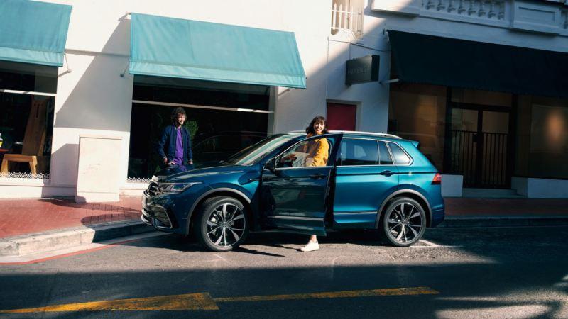Chica subiendo a un Volkswagen Tiguan azul aparcado en la calle