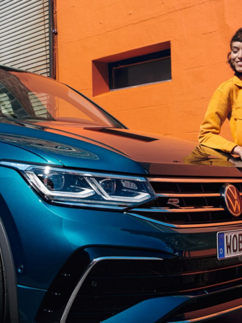 Chica sonriendo apoyada sobre el capó de un Volkswagen Tiguan azul metalizado a aparcado en la calle