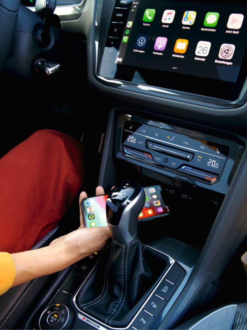 Detalle de la mano de una chica dejando el móvil en el compartimento del salpicadero y de la pantalla de App Connect
