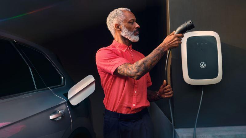 Hombre con un cargador Wallbox junto a un Volkswagen Touareg eHybrid aparcado