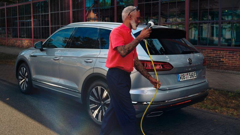 Hombre con el cable de un cargador eléctrico en la mano caminando detrás de un Volkswagen Touareg eHybrid aparcado en la calle